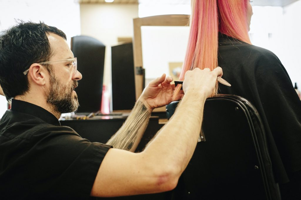 A hair stylist with a client, cutting her long straight hair, trimming the ends.