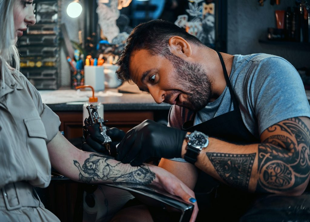 Tattoo master is creating new tattoo for customer